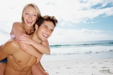 Man Giving Woman Piggyback Ride At The Beach